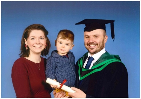 Male student in graduation robe pictured with family