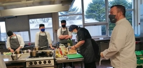 Catering students preparing food in kitchen
