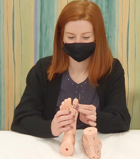 Student practising complementary therapy of training feet