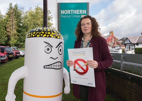 Female pictured with inflatable angry cigarette at College external sign
