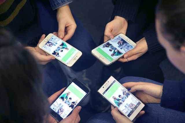 Four students holding mobile devices browsing College website.